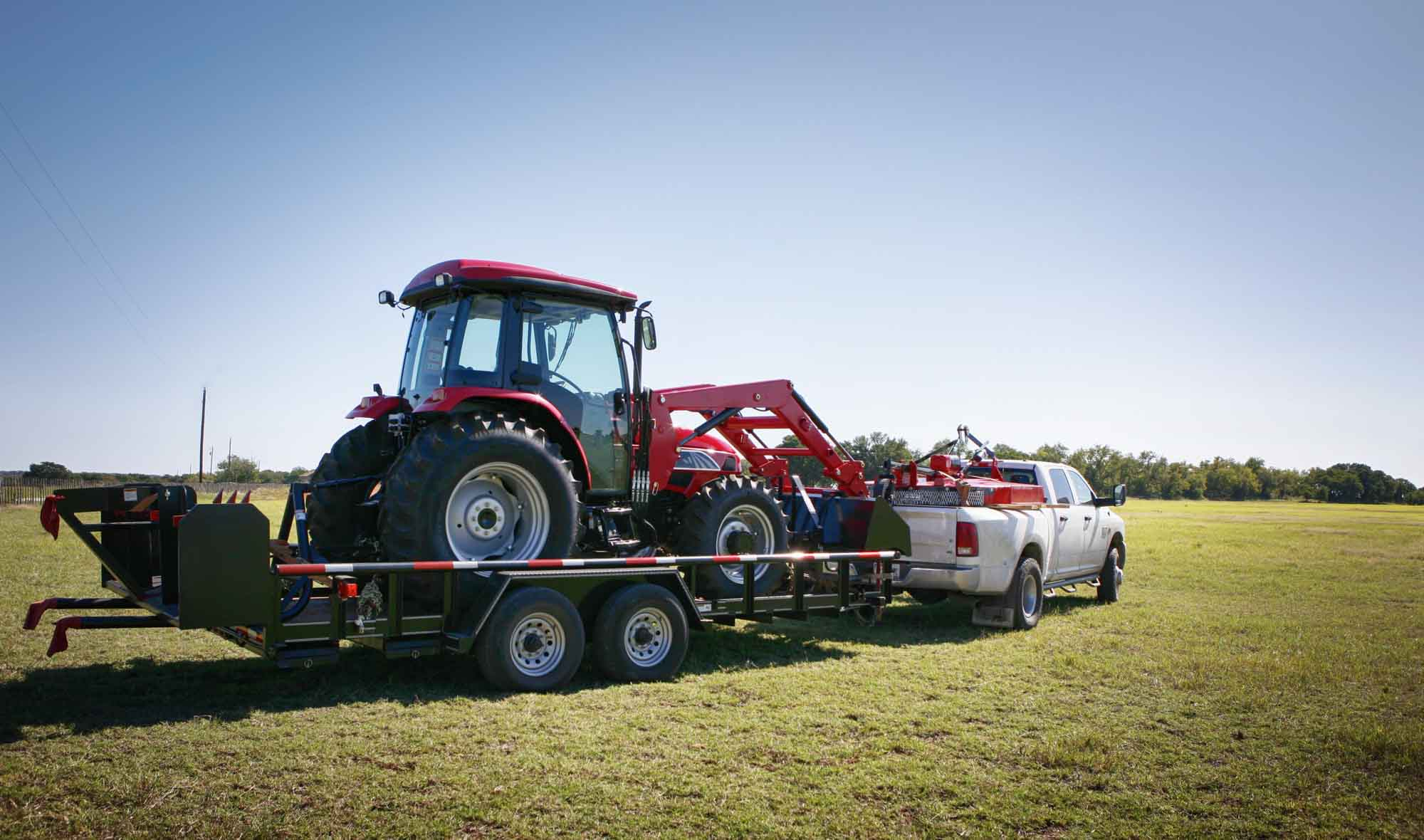 Texas farming: delivering/towing a large red tractor.